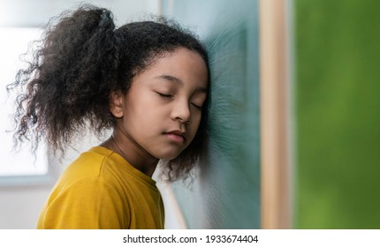 Portrait of sad little African girl lean head near the blackboard indoors. Kid is learning in class. Young student have tough day written with chalk on board. Stress painful study hard concept