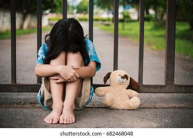 Portrait sad little Asian girl sitting on the floor.