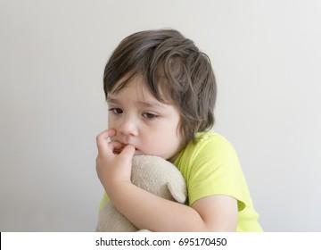 Portrait of sad little boy hugging teddy bear and put fingers in his mouth