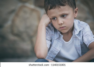 Portrait of sad little boy outdoors at the day time. Concept of sorrow.