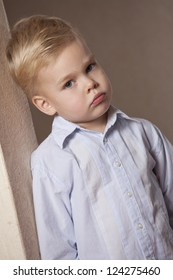 portrait of sad little boy in shirt standing at the wall