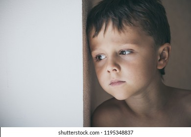 Portrait of sad little boy standing near the window  at the day time. Concept of sorrow.