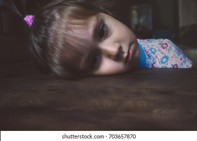 Portrait of sad little girl. girl bowed her head on the table and looks down before him. Face sad. The tired child lies with his head on a wooden table.