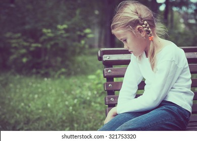 Portrait of sad little girl at the day time.