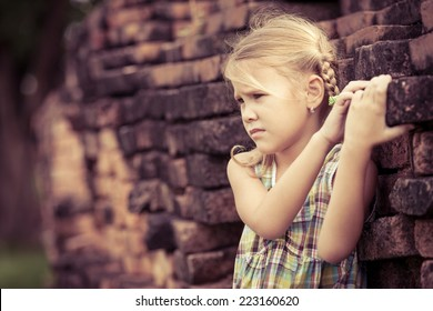 Portrait of sad little girl standing near the wall at the day time
