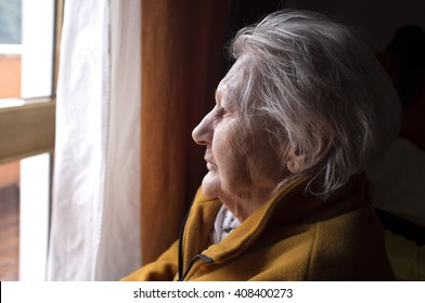 portrait of sad lonely pensive old senior woman looking in a window