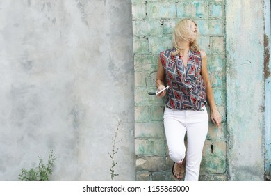 portrait of a sad lovely young blonde woman standing by the wall. deadpan style portrait. copy space