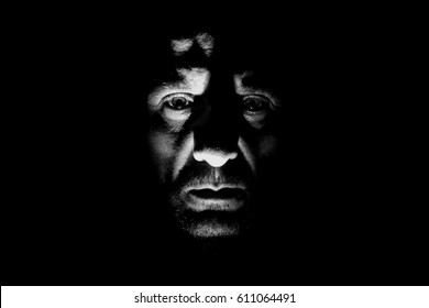 Portrait of sad man with chiaroscuro, craggy and marked face, wild man alone in the dark with high contrast, dark side of human, fugitive from justice, devil and gangster
