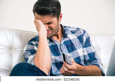 Portrait of a sad man holding bank card at home