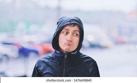 Portrait of a sad man in a raincoat and a hood in the rain. Bad stormy rainy weather concept