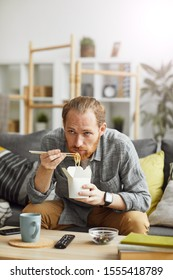Portrait of sad middle-aged man eating takeout noodles while watching TV at home in bachelors pad, copy space