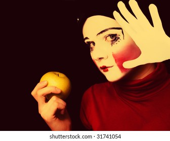 Portrait of the sad mime with an apple on a black background