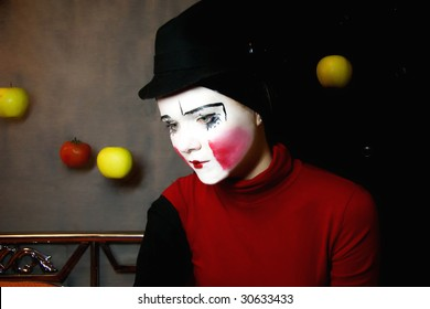 Portrait of the sad mime in a hat with apples