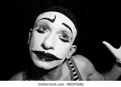 Portrait of sad mime on black background