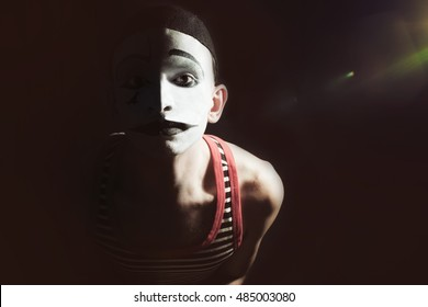 Portrait of sad mime wearing hat on black background