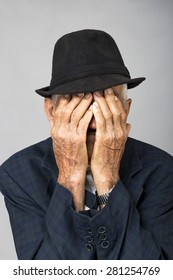 Portrait of a sad old man covering his face with hands over gray background