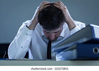 Portrait of sad, overworked businessman at his office