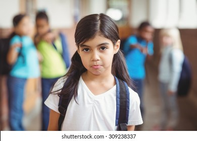 Portrait of sad pupil being bullied by classmates at corridor in school