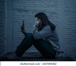 Portrait of sad scared young woman on the floor at night stressed and worried on smart mobile phone suffering cyber bullying harassment. desperate and depressed by being online abused by stalker.
