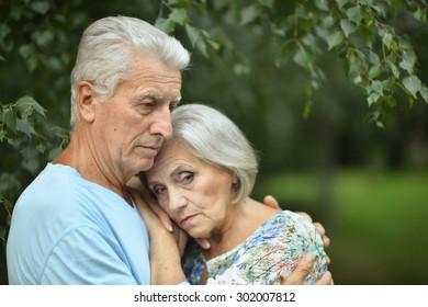 Portrait of a sad senior couple in summer park