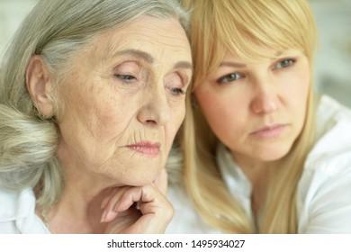 Portrait of sad senior woman with daughter