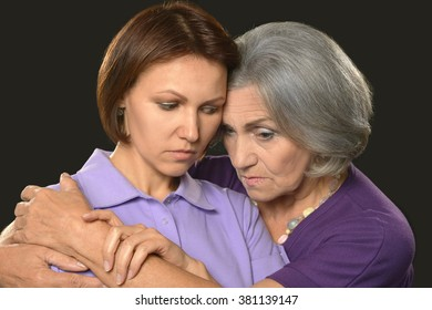 Portrait of sad Senior woman with daughter on black background