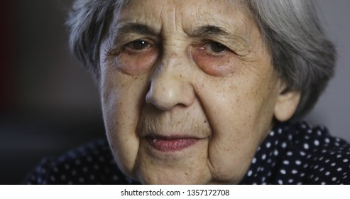 Portrait of a sad senior woman with deep wrinkles. Cute grandmother is looking at the camera.