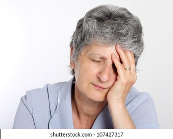 Portrait of a sad senior woman holding her head in pain