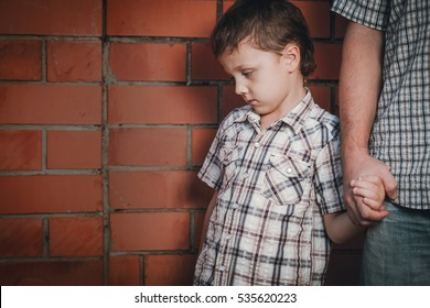 Portrait of sad son hugging his dad near wall at the day time