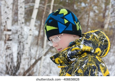 Portrait of a sad teenage boy with glasses, hat and jacket in the winter forest