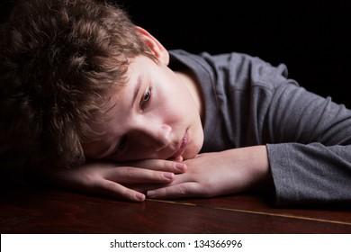 Portrait sad teenage boy on a black background