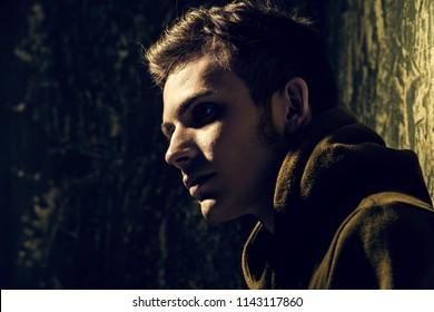 Portrait of a sad teenage boy over grunge background. Studio shot. Teen fashion.