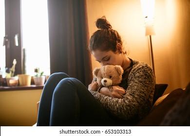 Portrait of a sad teenage girl hugging a teddy bear.