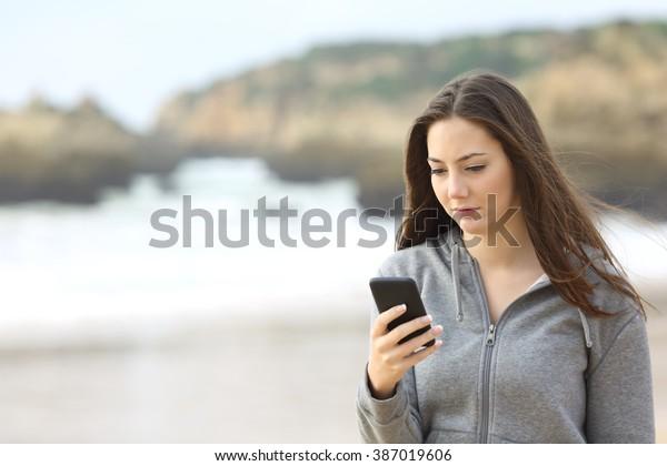 雨の日にメッセージを待つ携帯電話を、海辺を歩く悲しい十代の子のポートレートがオンラインでチェックしている