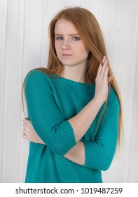 Portrait of a sad and tired young beautiful woman with her flowing red hair, dressed in a turquoise sweater, looking into the camera pulling back a strand of hair against a light wooden wall