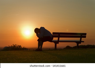 Portrait of a Sad or unhappy man sitting on a bench at Sunset