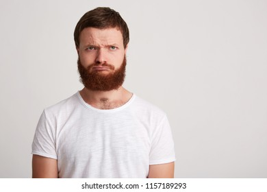 Portrait of sad upset young man hipster with beard wears t shirt feels displeased and depressed isolated over white background Thinking about his problems