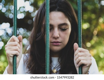 Portrait of sad woman behind prison bars