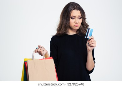 Portrait of a sad woman holding shopping bags and bank card isolated on a white background