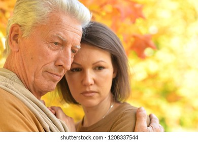 Portrait of sad woman and senior man hugging