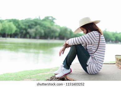 Portrait of a sad woman sitting on green grass in a spring garden.