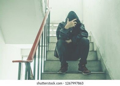 Portrait of sad young man covering his face with hands sitting on old stairs. Selective focus on hands. Sadness, despair, dark, concept