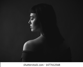 Portrait of sad young woman with bare shoulders. Black and white. From back