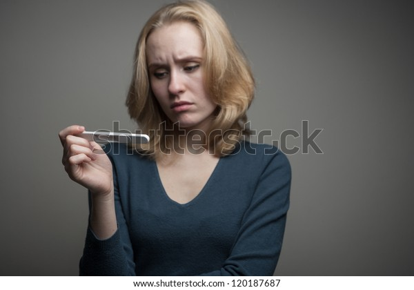 portrait of a sad young woman looking at pregnancy test with bad news