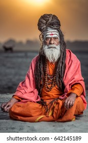 Portrait of sadhu sitting with sunrise behind him, Varanasi, India.