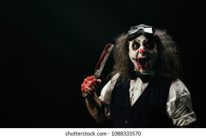 Portrait of a sadistic clown, a bloody knife in his hand
