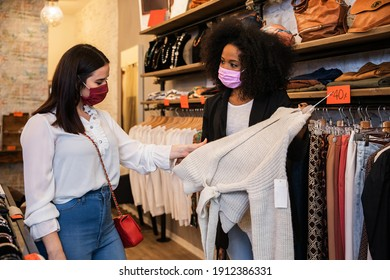 Portrait of a saleswoman and owner showing a dress to a customer in a store - Millennial people wearing protective masks against Coronavirus infection, Covid-19 - Concept of sales assistants