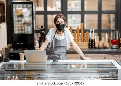 Porträt einer Verkäuferin oder eines kleinen Unternehmers mit medizinischer Maske an der Theke im Café oder kleinen Laden. Konzept eines Einzelhandelsgeschäfts während einer Pandemie