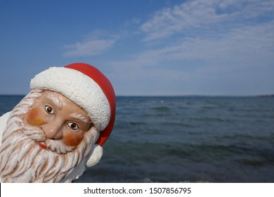 Portrait of Santa Claus. Christmas by the sea. Christmas garden gnome with Santa hat looks around the corner  on vacation in the tropics  (Not copyrighted)