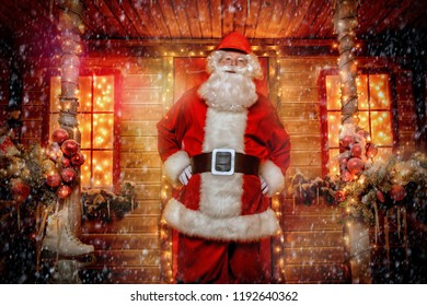 Portrait of Santa Claus in the courtyard of his house decorated with Christmas lights. Christmas and New Year concept.